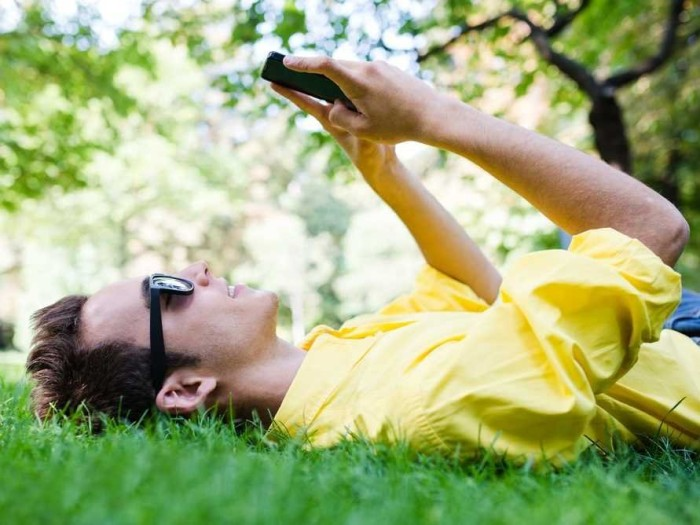 man-in-sunglasses-texting-on-grass-3